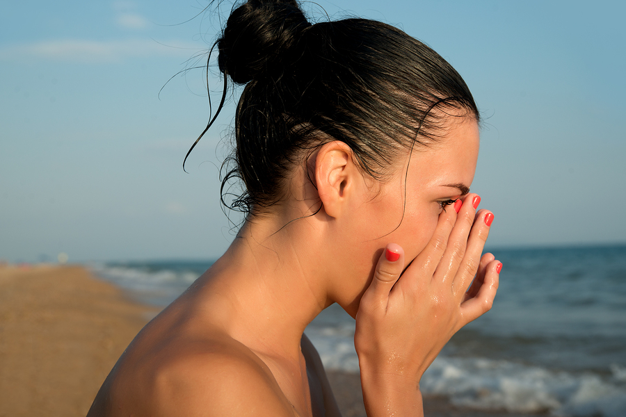 woman rubbing her eyes at the beach
